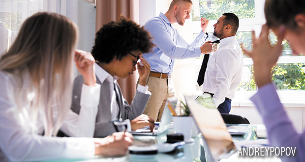 Stressed Businesspeople Sitting In Front Of Two Colleagues Fighting In Office